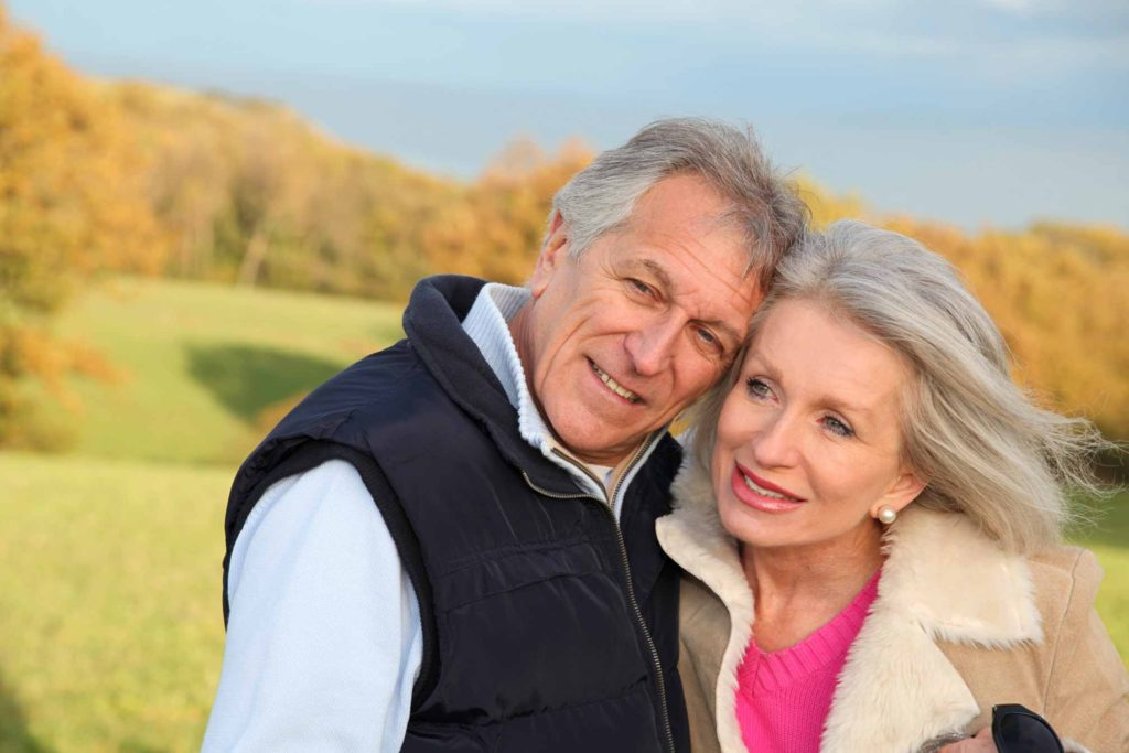 Photo of happy older couple with wind in their hair.